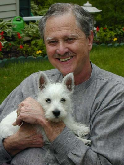 Art wearing a gray shirt, holding his West Highland Terrier Duncan.
