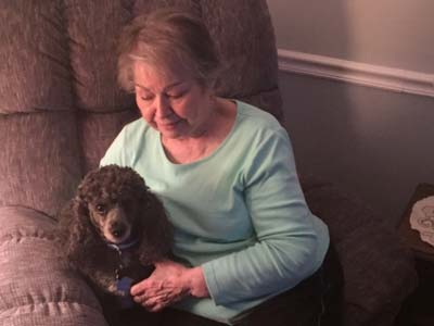 Barb holding her dog Tuxedo in a comfy recliner.
